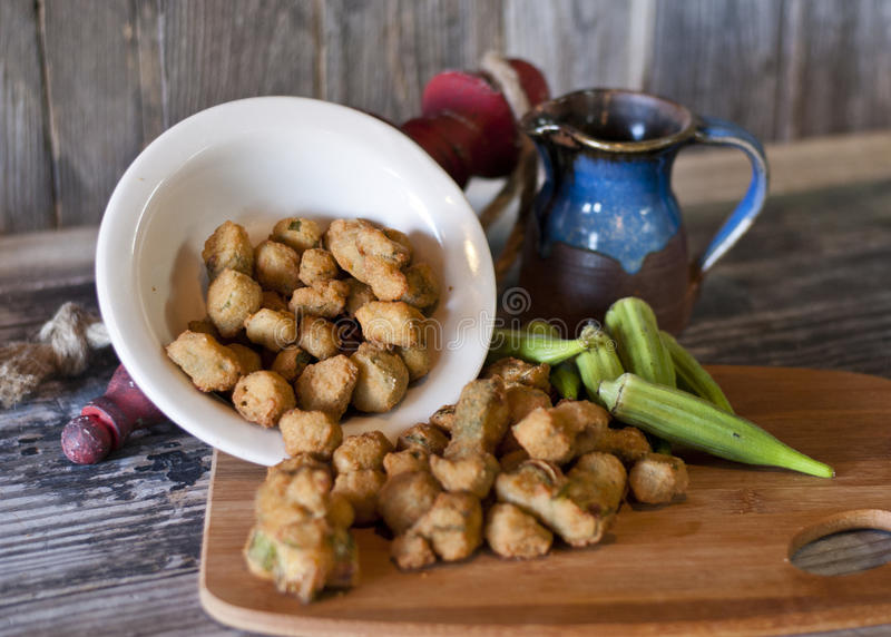 Fried Okra. Battered and Fried Okra nuggets tumbling from a white dish onto cutting board stock photography