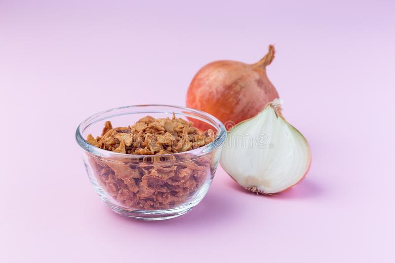 Fried onion in the glass, topping for hot dog, fast food, horizontal on  pink background stock photo