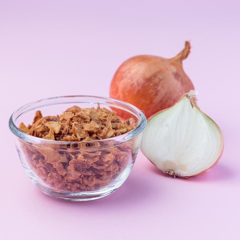 Fried onion in the glass, topping for hot dog, fast food, on pink background, square format. Fried onion in the glass, topping for hot dog, fast food, on a pink stock images