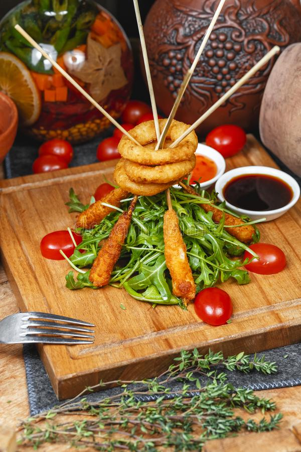Fried onion rings and sausages on skewers in beer batter, served with arugula leaves and fresh cherry tomatoes in Georgian style. National cuisine royalty free stock image
