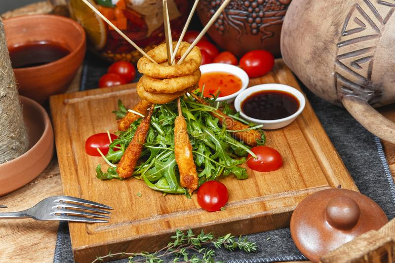 Fried onion rings and sausages on skewers in beer batter, served with arugula leaves and fresh cherry tomatoes in Georgian style. National cuisine stock images