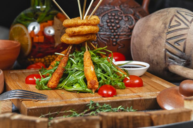 Fried onion rings and sausages on skewers in beer batter, served with arugula leaves and fresh cherry tomatoes in Georgian style. National cuisine royalty free stock images