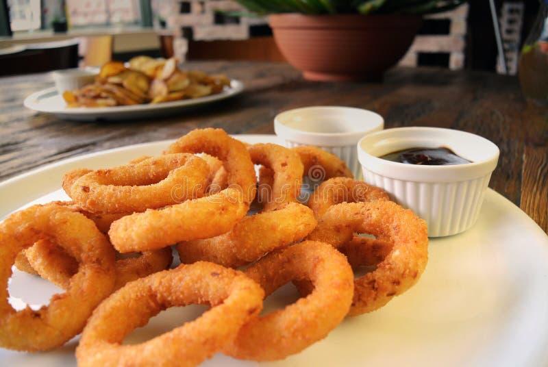 Fried Onion Rings und Soßen auf Holztisch lizenzfreies stockbild