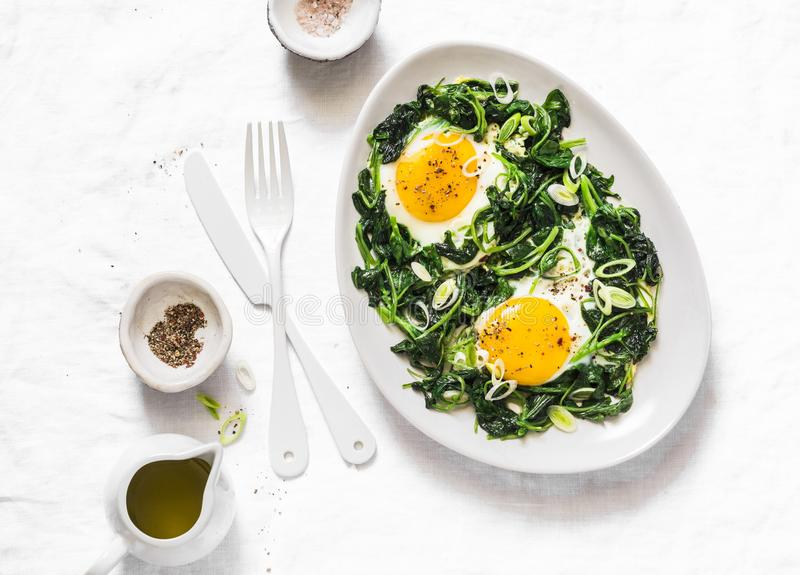 Fried organic farm eggs with spinach - healthy breakfast on a light background stock image