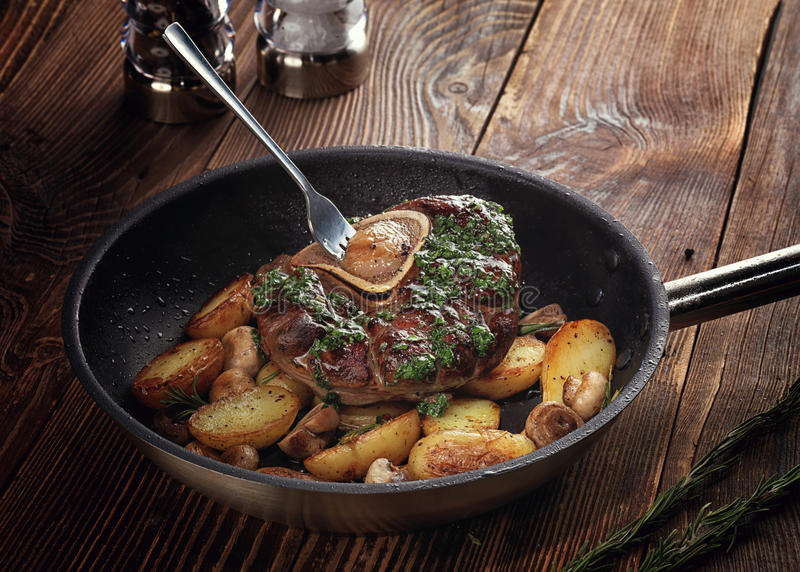 Fried ossobuco with vegetable ragout of potatoes and mushrooms. stock photography