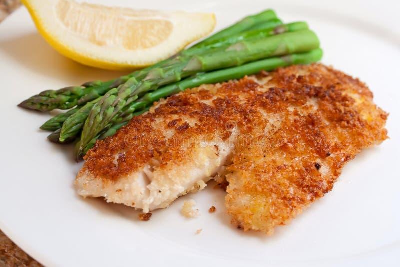 Fried panerade fisken med sparrisen och citronen royaltyfri bild