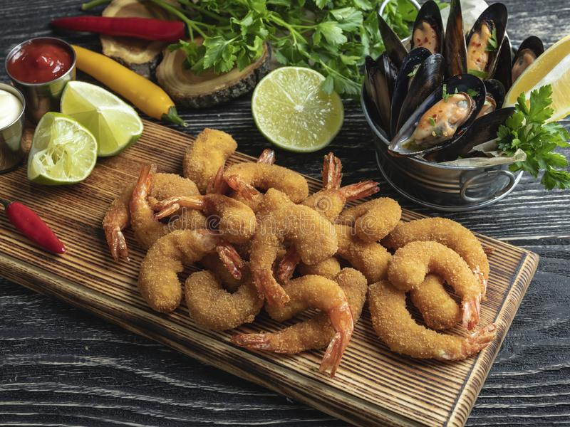 Fried panerade räkor, musslor tjänade som med limefrukt på träbrädet, läcker djup, röd vit sås arkivfoto