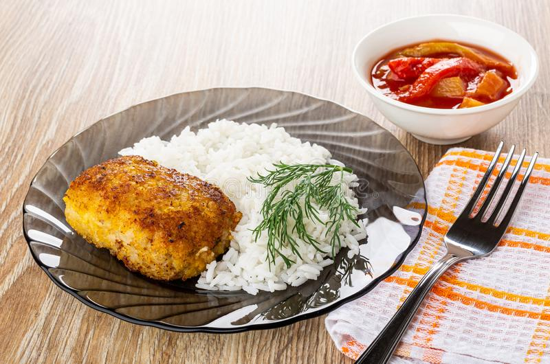 Fried patty with rice in brown plate, bowl with lecho, fork on napkin on wooden table. Fried patty with rice and dill in transparent brown plate, bowl with lecho royalty free stock image