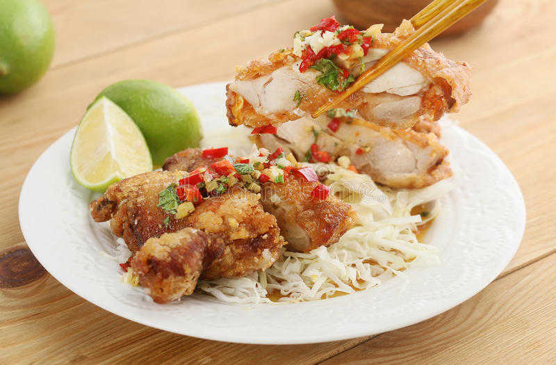 Fried pepper chicken with salad and sliced lime on white plate o stock images