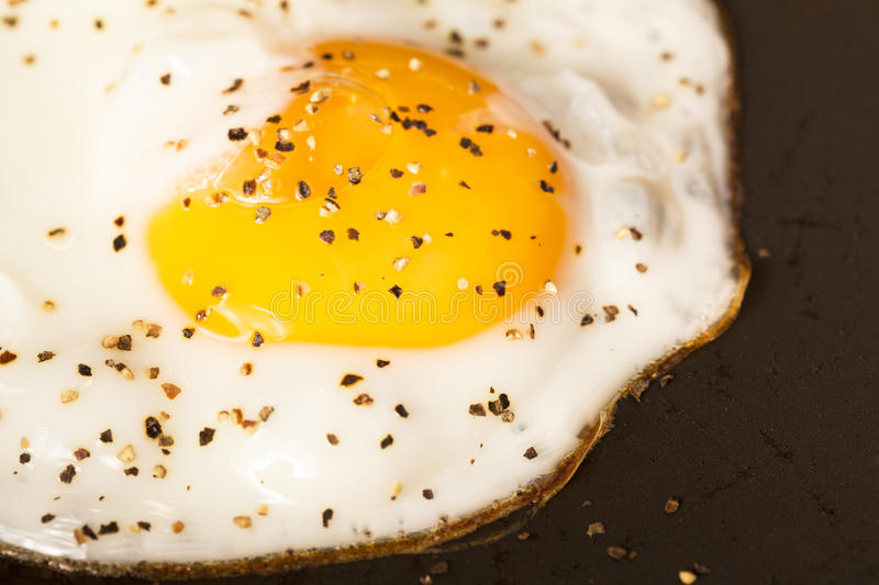 Fried peppered egg in pan royalty free stock photography