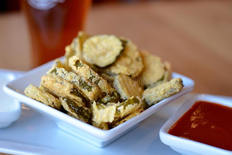 Fried Pickle Chips. Fried pickles with hot sauce royalty free stock photography