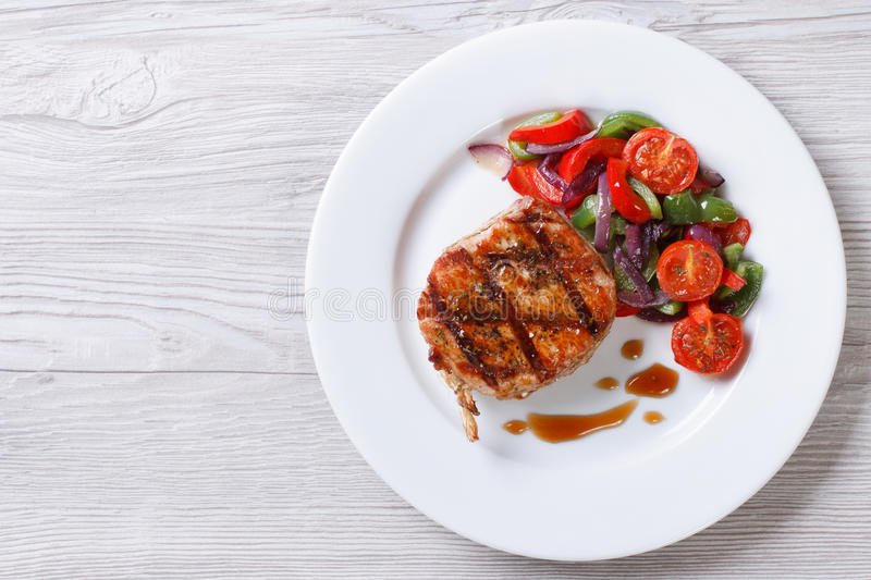 Fried piece of pork with vegetable salad, top view horizontal stock photo