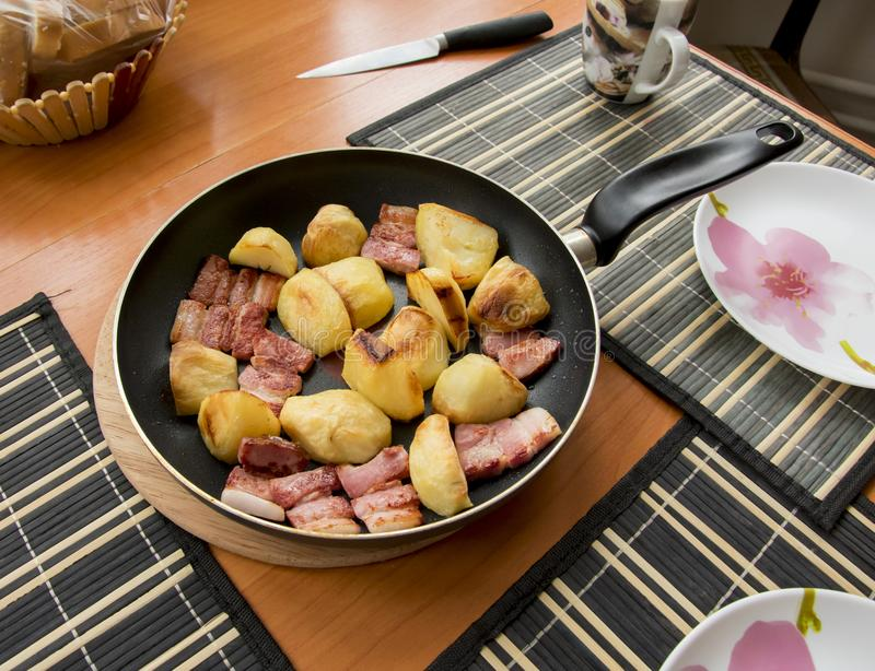 Fried pieces of baked golden potatoes and red shiny, from molte. N fat, bacon slices royalty free stock photography