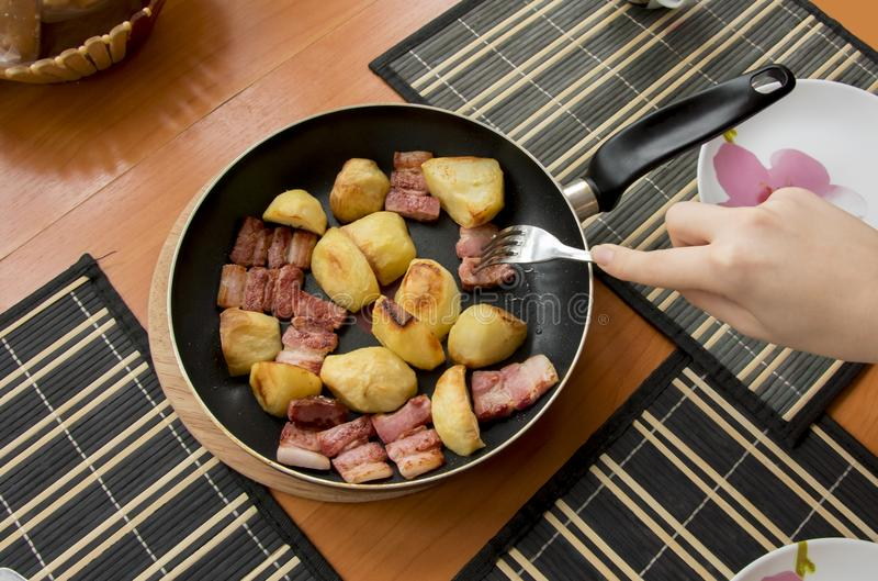 Fried pieces of baked golden potatoes and red shiny, from molte. N fat, bacon slices stock image