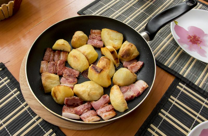 Fried pieces of baked golden potatoes and red shiny, from molte. N fat, bacon slices royalty free stock images