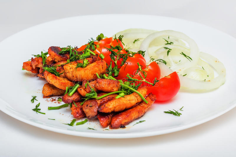 Fried pieces of pork schnitzel with cherry tomatoes, onion rings. And greens on white plate royalty free stock image