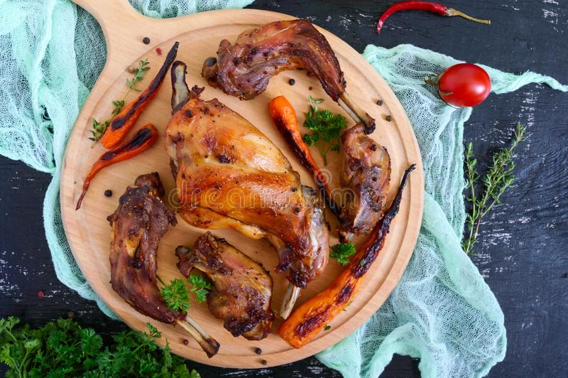 Fried pieces of rabbit with vegetables on a wooden tray on a dark background royalty free stock images