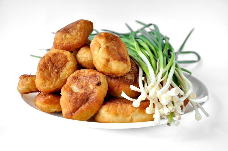 Fried pies with garlic stuffed on a white plate. Fried pies with filling on a white plate with garlic. On a white background royalty free stock photo