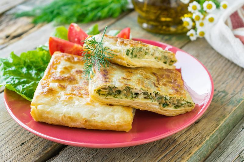 Fried pita bread stuffed with chicken, cheese and herbs served on a ceramic plate. Wooden background. Selective focus stock photo