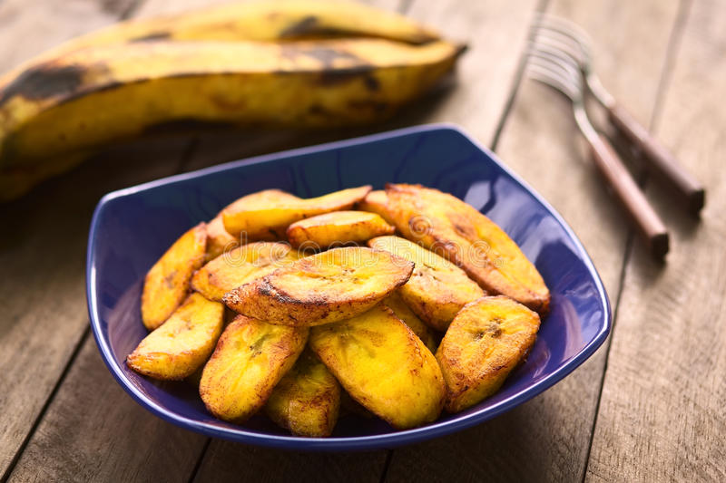 Fried Plantain. Slices of fried ripe plantain in blue bowl, which can be eaten as snack or is used to accompany dishes in some South American countries, ripe royalty free stock photo