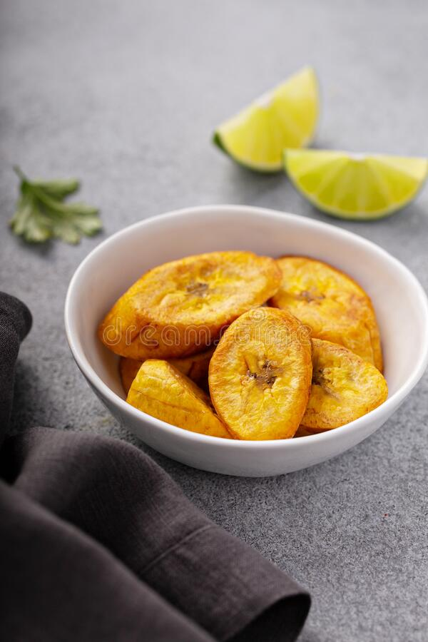 Fried plantains, carribean cuisine. Fried plantains with fresh lime in the background, carribean cuisine royalty free stock photos