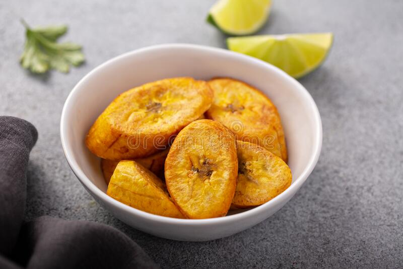Fried plantains, carribean cuisine. Fried plantains with fresh lime in the background, carribean cuisine royalty free stock image