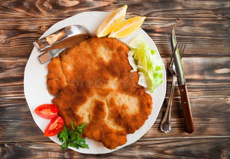 Fried pork chop coat in breadcrumbs with lemon slise and vegetable salad stock images