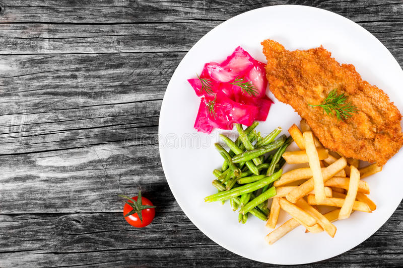 Fried pork chop with french fries, green bean and salad. Bread Crumb Coated fried pork chop with french fries, fried green bean and salad with dill and cabbage royalty free stock photos
