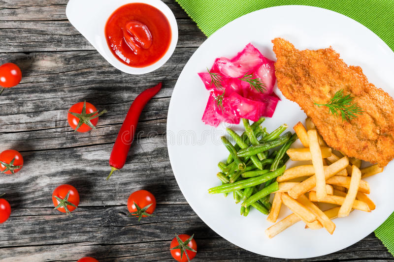 Fried pork chop with french fries, green bean and salad. Bread Crumb Coated fried pork chop with french fries, fried green bean and salad with dill and cabbage royalty free stock image