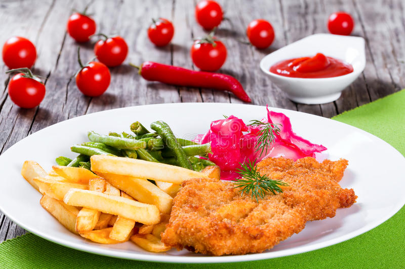 Fried pork chop with french fries, green bean and salad. Bread Crumb Coated fried pork chop with french fries, fried green bean and salad with dill and cabbage royalty free stock photography