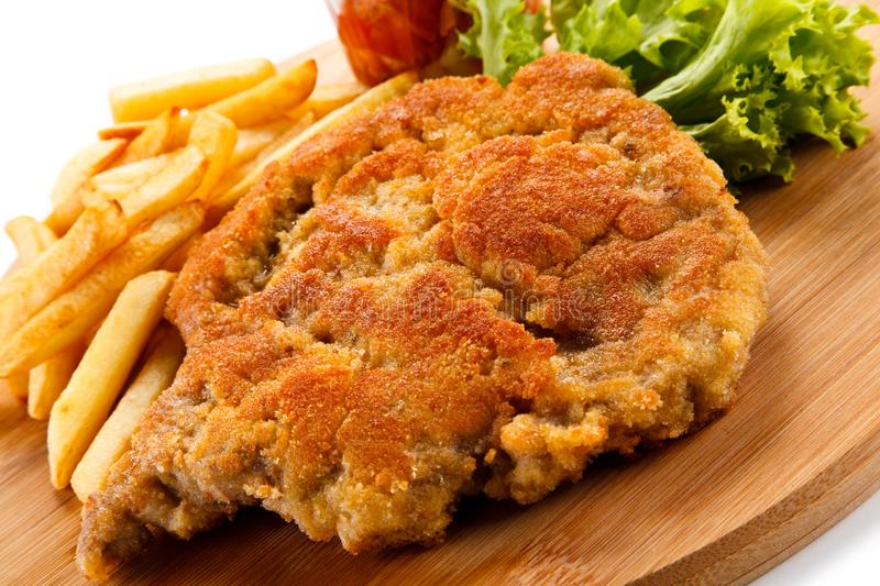 Fried pork chop with french fries. On white background stock photography