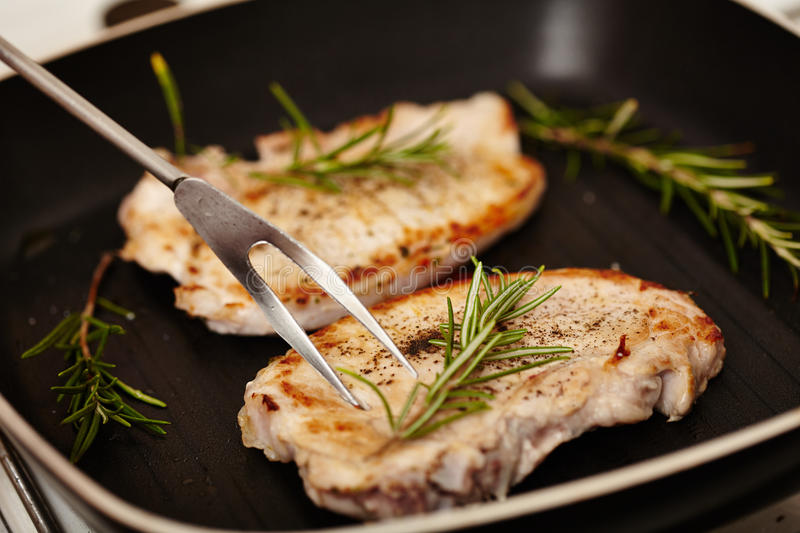 Fried pork chops in the frying pan decorated with rosemary royalty free stock photography