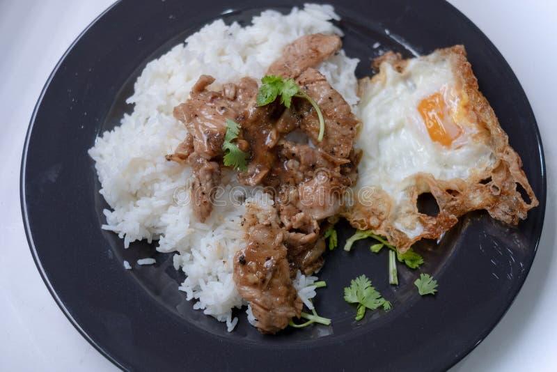 Fried Pork con il pepe dell'aglio e l'uovo fritto su riso immagini stock