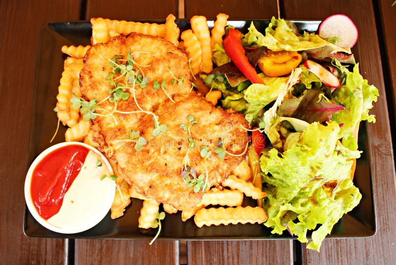 Fried pork, french fries and assorted fresh vegetables ketchup and mayonnaise royalty free stock photo