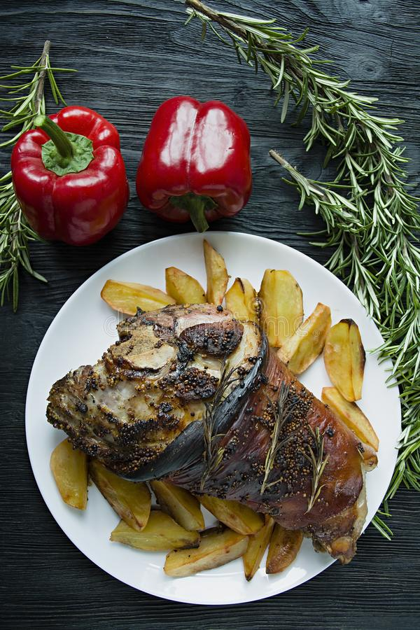 Fried pork knuckle with potatoes served on a white plate. Decorated with fresh Bulgarian pepper, rosemary. Dark wooden background. View from above royalty free stock image