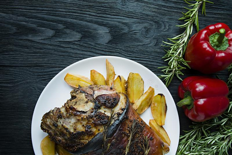 Fried pork knuckle with potatoes served on a white plate. Decorated with fresh Bulgarian pepper, rosemary. Dark wooden background. View from above stock images