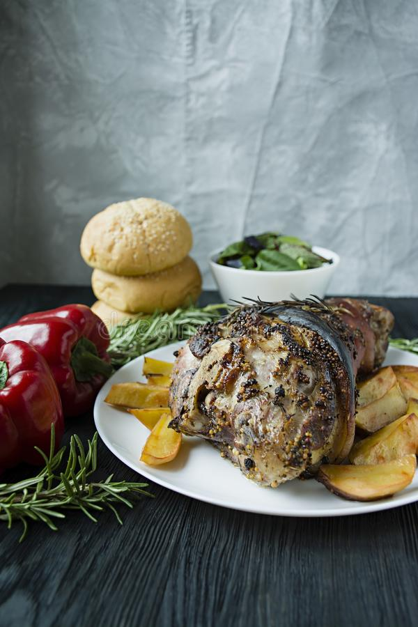 Fried pork knuckle with potatoes served on a white plate. Decorated with fresh Bulgarian pepper, rosemary. Dark wooden background. View from above stock photography