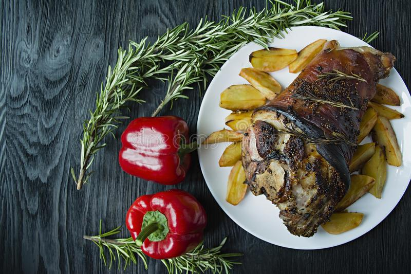 Fried pork knuckle with potatoes served on a white plate. Decorated with fresh Bulgarian pepper, rosemary. Dark wooden background. View from above stock photos