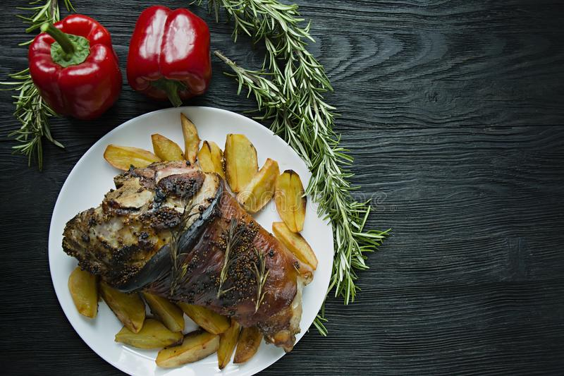 Fried pork knuckle with potatoes served on a white plate. Decorated with fresh Bulgarian pepper, rosemary. Dark wooden background. View from above stock photo