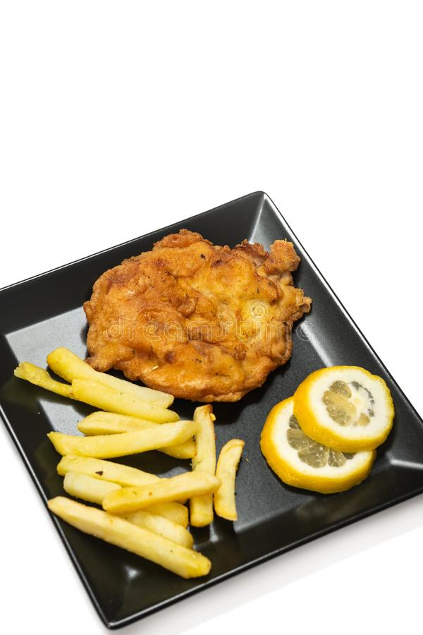Fried pork meat steak with lemon on the plate stock image