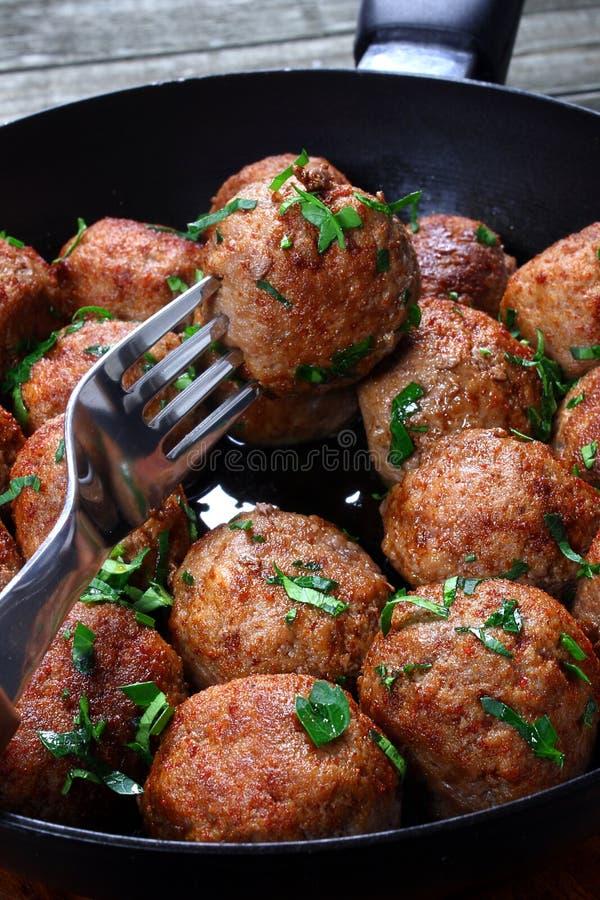 Fried pork meatballs. In frying pan stock image