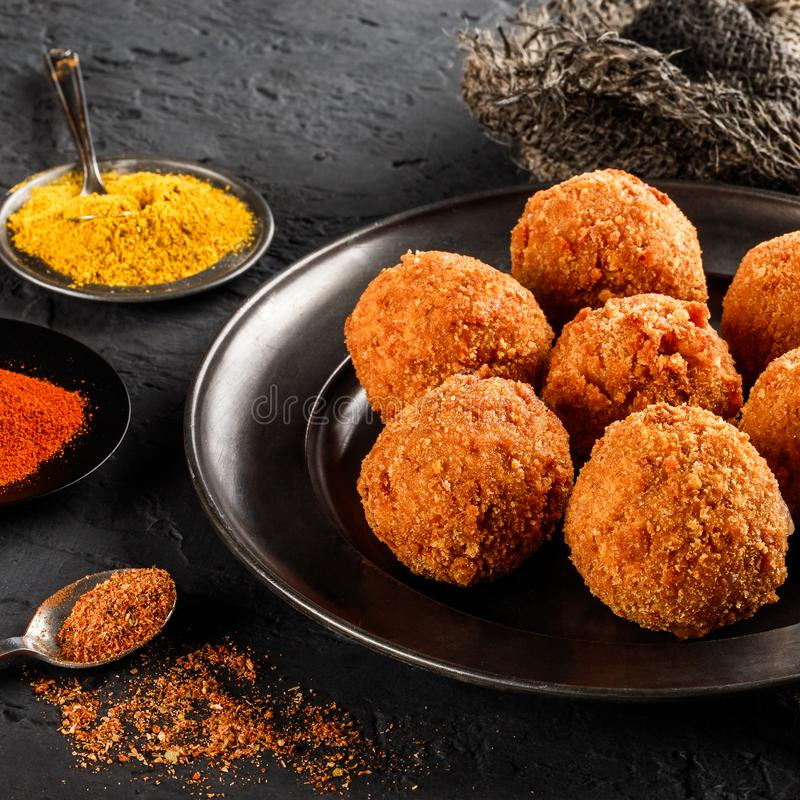 Fried potato cheese balls or croquettes with spices on black plate over dark stone background. Unhealthy food, top view.  royalty free stock image