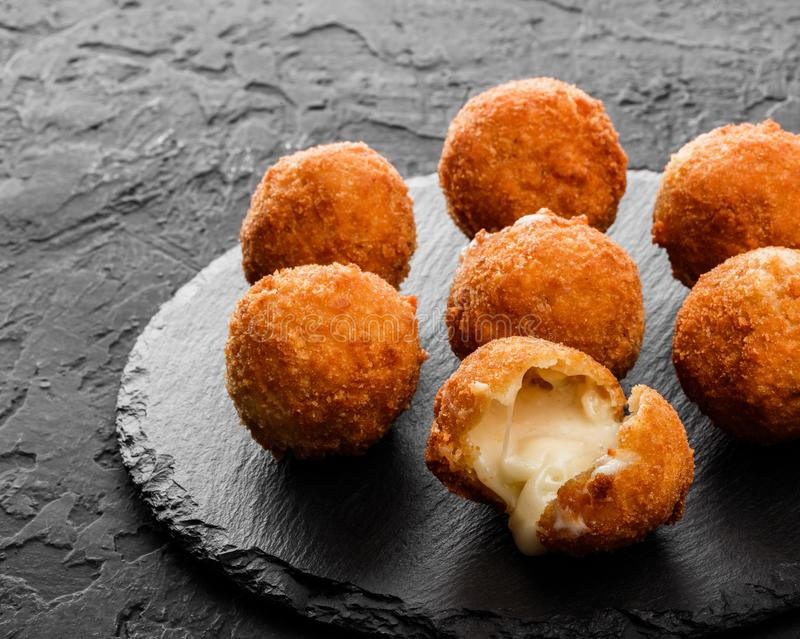 Fried potato cheese balls or croquettes with spices on black plate over dark stone background. Unhealthy food, top view stock photography