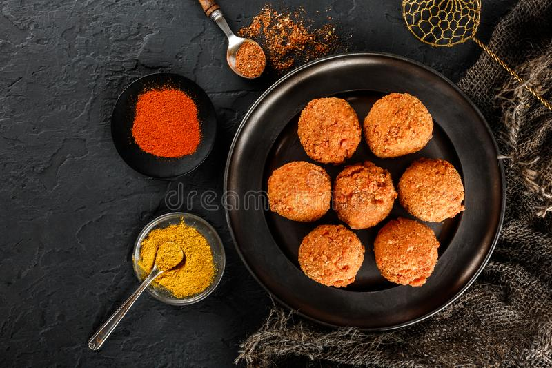 Fried potato cheese balls or croquettes with spices on black plate over dark stone background. Unhealthy food, top view.  royalty free stock photography