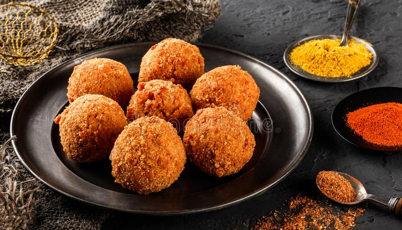 Fried potato cheese balls or croquettes with spices on black plate over dark stone background. Unhealthy food, top view stock photo