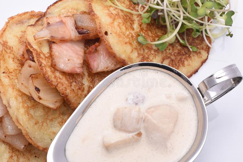 Fried potato pancakes with bacon and mushroom sauce royalty free stock photography