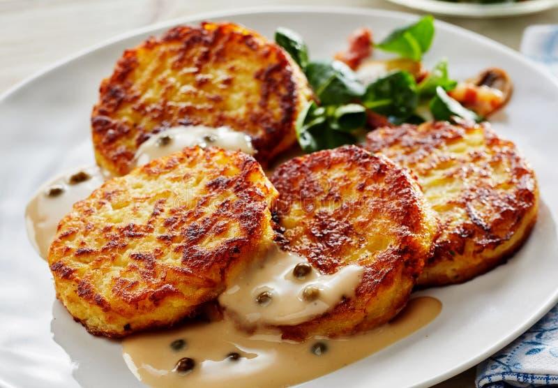 Fried Potato Pancakes en sauce crémeuse avec de la salade image stock