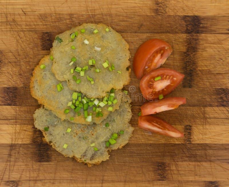 Fried Potato Pancakes fait maison aux oignons verts coupés sur le conseil en bois image libre de droits