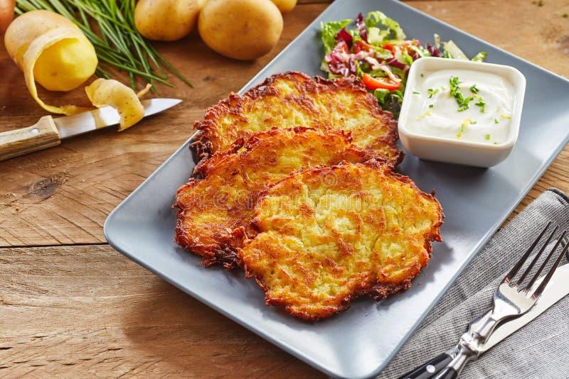Fried Potato Rosti Served croquant avec de la salade et l'immersion images stock