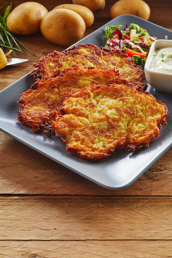 Fried Potato Rosti Served quebradizo con la ensalada y la inmersión fotografía de archivo libre de regalías